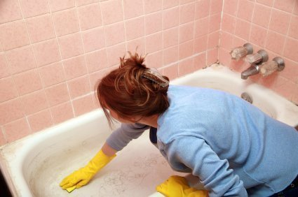 Woman with rubber gloves cleaning the tub